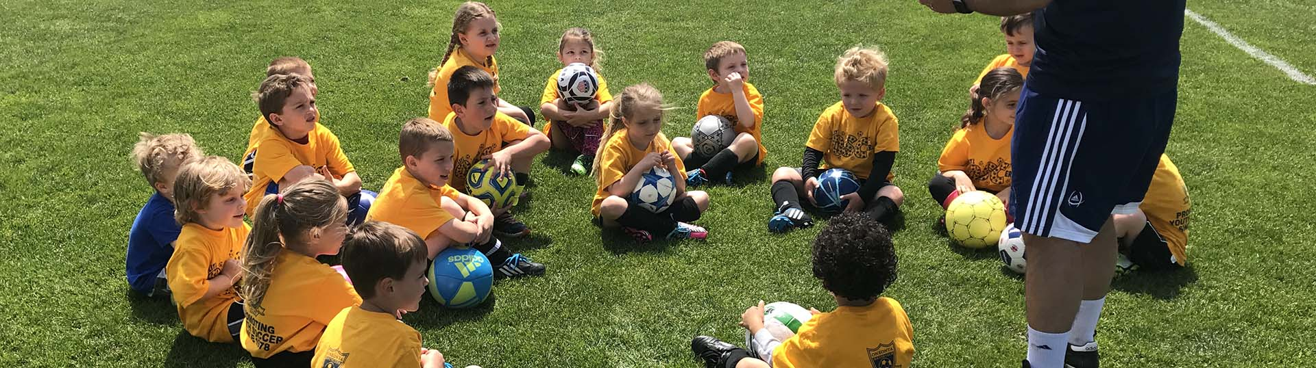 Lil OSC'ers sit in a huddle listening to their coach